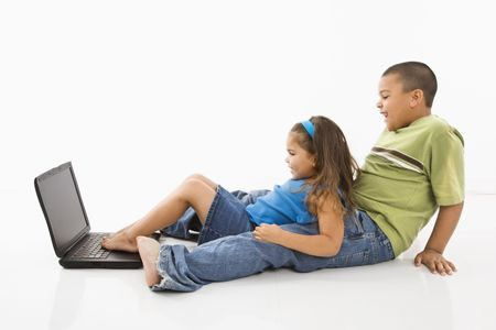 Brother and sister putting feet on laptop computer and smiling. Stock Photo - 3569381