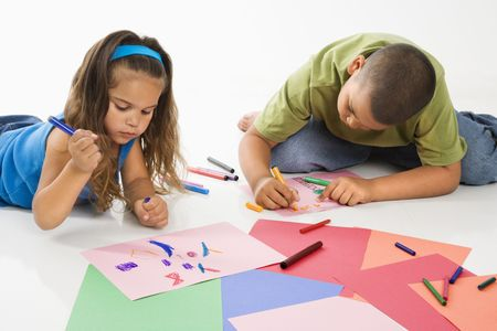 Young latino boy and girl coloring on construction paper and smiling. photo