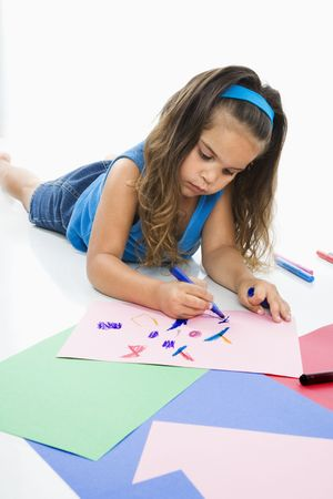 Young latino girl coloring on construction paper.
