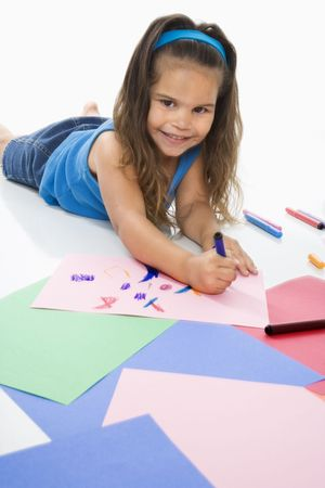 Young latino girl coloring on construction paper and smiling. Stock Photo
