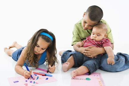 Young latino girl coloring on construction paper while brothers watch. photo