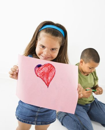 Young girl showing off drawing of heart while boy sits behind her. photo