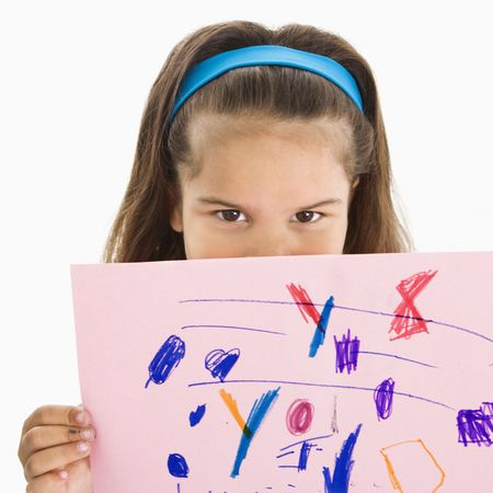Young girl holding drawing over mouth.. photo