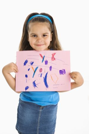 Smiling hispanic girl proudly holding drawing. photo