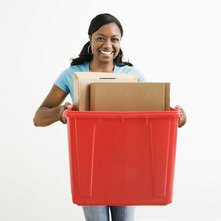 African American young adult female holding recycling bin with cardboard in it. photo