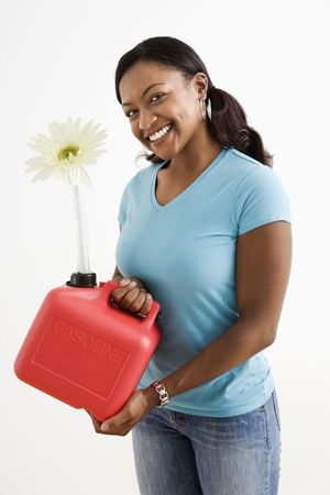 African American young adult female holding gas can with flower in its nozzle. photo