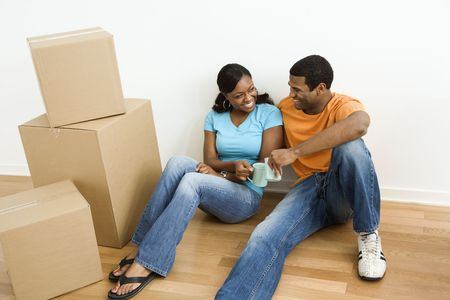 African American male and female couple sitting on floor next to moving boxes relaxing. photo