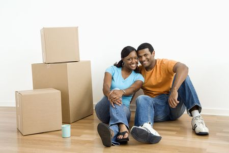 African American male and female couple sitting on floor next to moving boxes. photo