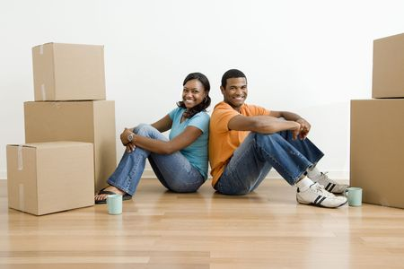 unpacking: African American male and female couple sitting on floor next to moving boxes.