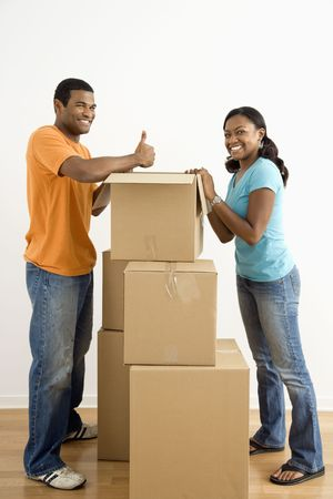 African American male and female couple packing cardboard boxes. photo