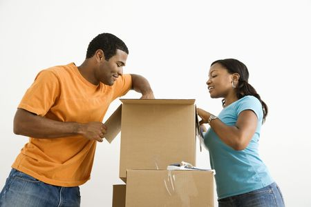 African American male and female couple packing cardboard boxes. Stock Photo