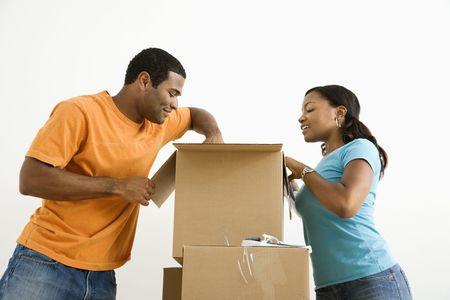 cajas de carton: African American masculino y femenino par de embalaje, cajas de cart�n. Foto de archivo