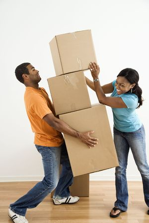 man carrying: African American female placing boxes on large stack man is holding.
