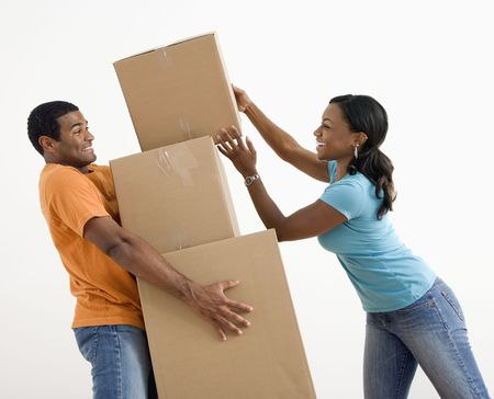 African American woman placing boxes on large stack man is holding. Stock Photo - 3589379