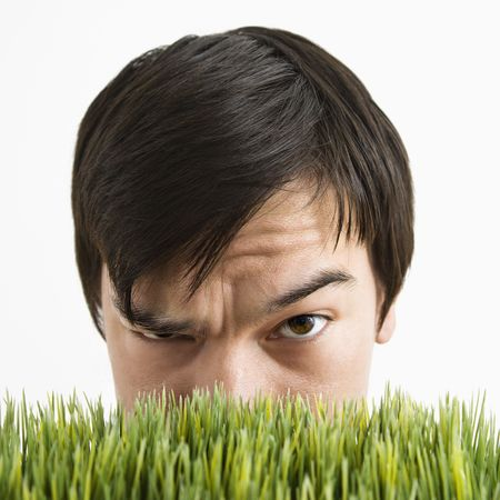 cocked: Asian young man looking over grass with eyebrow cocked.