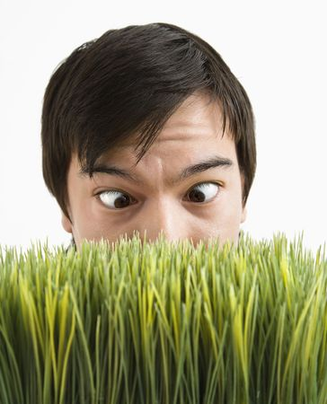 Asian young man looking over grass with eyes crossed. Stock Photo
