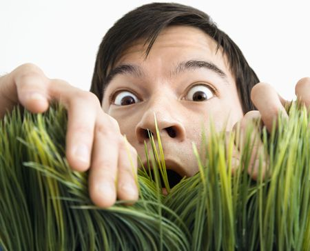 Asian young man looking through grass with fearful expression.