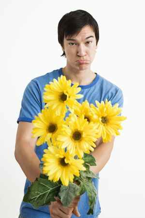 Asian young man holding bouquet of yellow gerber daisies with pout on his face. photo