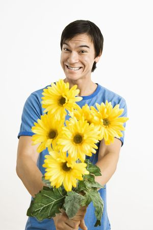 wooing: Asian young man holding bouquet of yellow gerber daisies smiling.