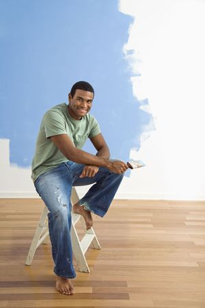 African American young man sitting next to half-painted wall with paintbrush. Stock Photo - 3589378