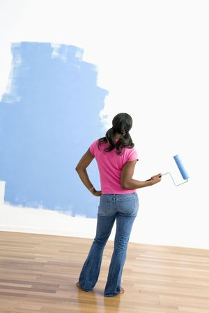 African American young woman standing next to half-painted wall with paint roller. photo