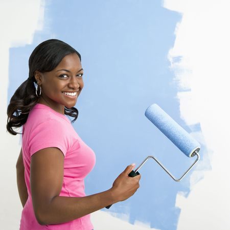 African American woman painting wall blue smiling at viewer. photo
