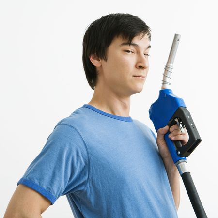 Asian young man holding gasoline pump nozzle. photo