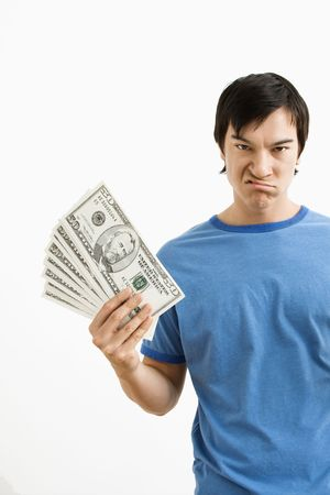 Asian young man holding money with disgust on his face. photo