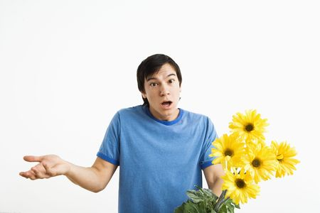 Asian young man holding bouquet of yellow gerber daisies shrugging. Stock Photo