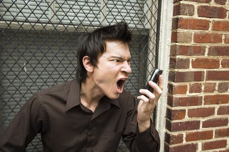 Angry young Asian man next to brick wall and window yelling at cell phone. photo