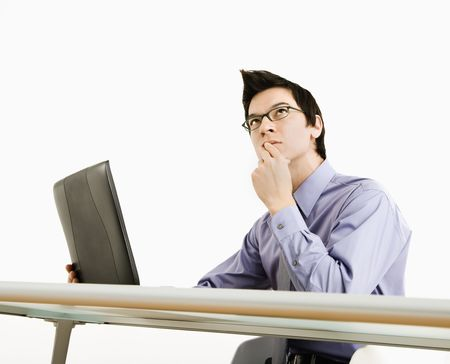 Asian businessman sitting at desk working on laptop thinking.