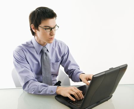 Asian businessman sitting at desk working on laptop computer. Stock Photo - 3589225