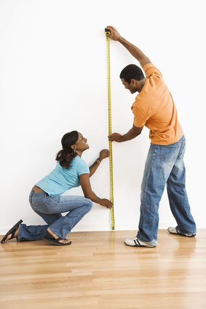 African American male and female measuring wall. photo