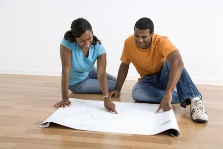 African American couple sitting on floor looking at architectural blueprints. photo