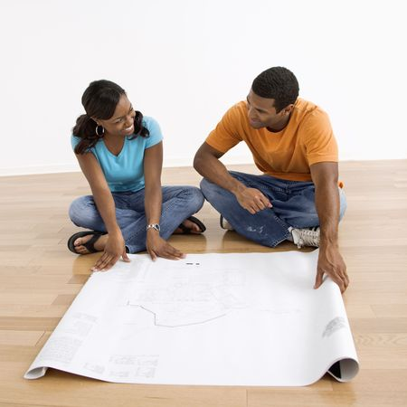 African American couple sitting on floor looking at architectural blueprints. Stock Photo - 3589231