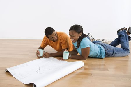 African American couple lying on floor looking at architectural blueprints. photo