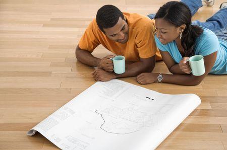 couple afro americain: African American couple allong� sur le plancher � la recherche de plans architecturaux. Banque d'images