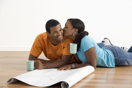 African American female kissing man next to blueprints. photo