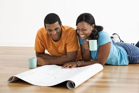 African American male and female couple lying on floor looking at architectural  blueprints. Stock Photo