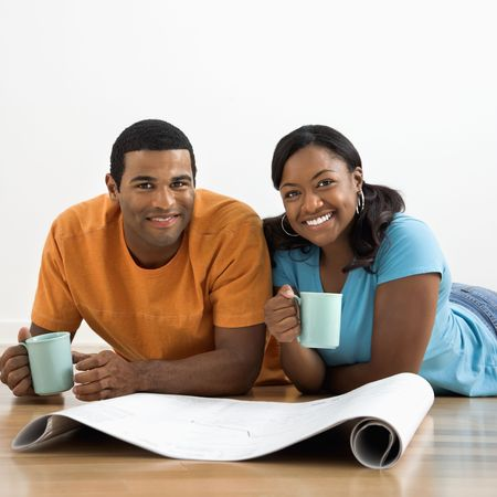 African American male and female couple with architectural  blueprints drinking coffee. Stock Photo