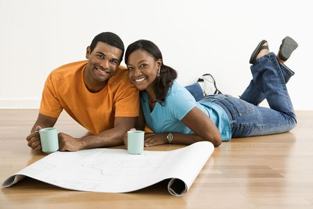 African American male and female couple with architectural  blueprints drinking coffee. photo