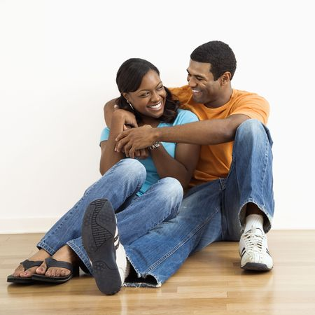 snuggling: Happy, smiling African American couple sitting on floor snuggling.