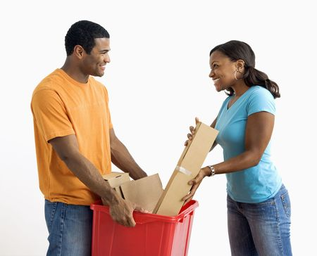 African American male holding recycling bin while pretty female puts cardboard in. photo