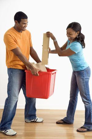 Male holding recycling bin while pretty female puts cardboard in. photo