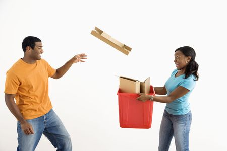 Male holding recycling bin while pretty female puts cardboard in. Stock Photo - 3589217