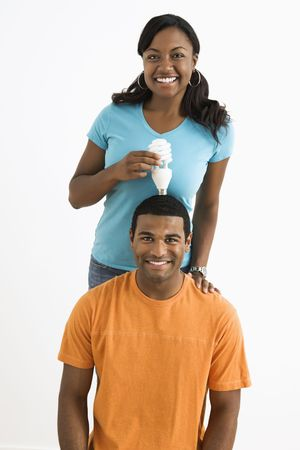African American female holding energy-saving lightbulb over  mans head. photo