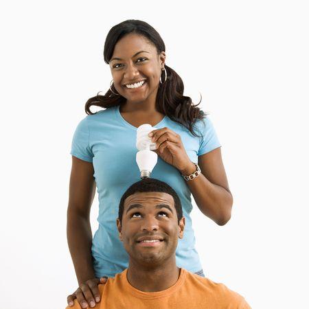 African American female holding energy-saving lightbulb over  man's head. Stock Photo - 3589207