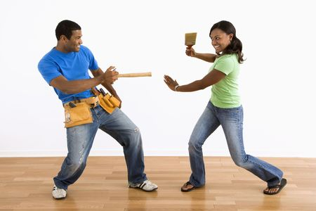 African American man and woman play fighting with household tools. photo