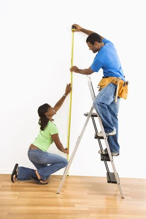 African American man and woman measuring wall at home. photo