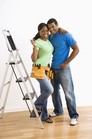 home repair: Portrait of smiling African American male and female couple with home repair tools and ladder. Stock Photo